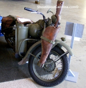 Vintage Harley motorcycle and rifle