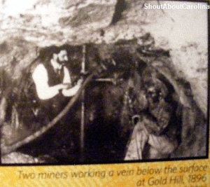 Old photo of gold miners working under a vein in Gold Hill NC